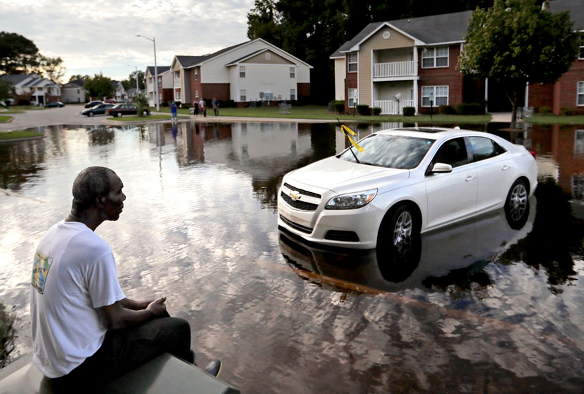 Augustin Dieudomme looks out at the flooded entrance to his apartment complex as it continues to rise in the aftermath of Hurricane Florence in Fayetteville, N.C., Sept. 18, 2018. (AP/David Goldman)