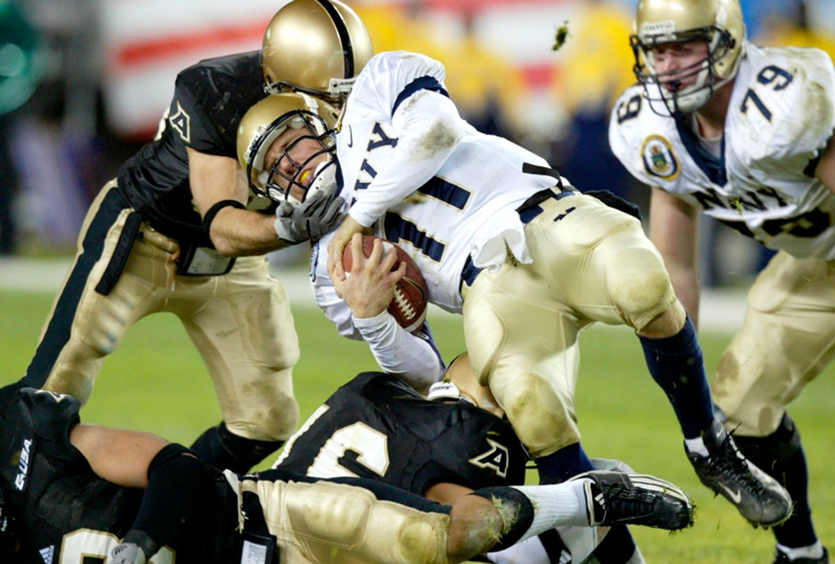 An unidentified Army defender pulls down Navy quarterback Craig Candeto (11)  in the third quarter the 104th Army-Navy football game, Dec. 6, 2003.  (AP/Rusty Kennedy)