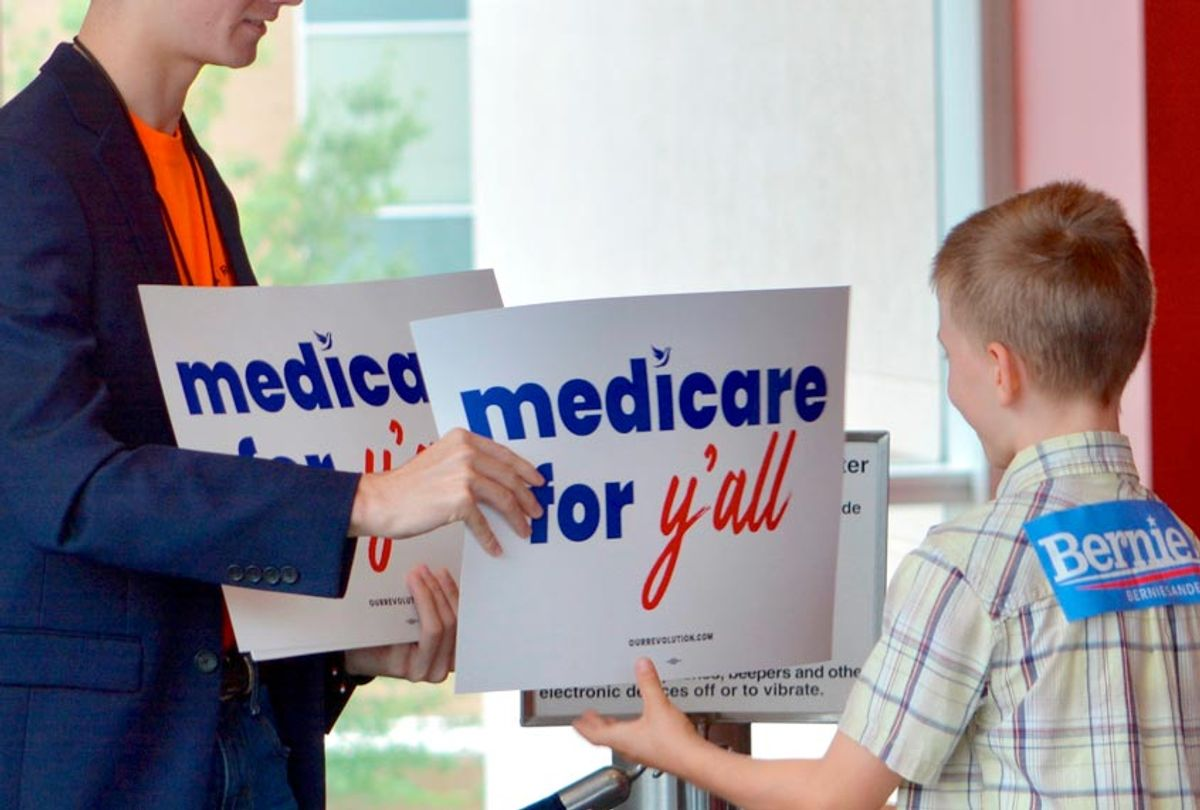 """A volunteer hands out a poster as Vermont independent Sen. Bernie Sanders was set to address a """"Medicare for All"""" rally in downtown Columbia, S.C. on Saturday, Oct. 20, 2018 (AP/Meg Kinnard)"""