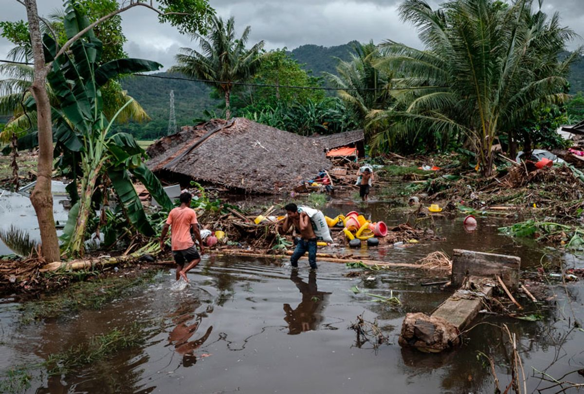 Villagers walk through debris after being hit by a tsunami as they carry their belongings on December 24, 2018 in Carita, Banten province, Indonesia. (Getty/Ulet Ifansasti)