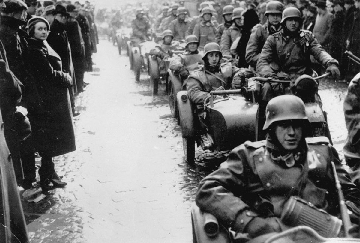 German Nazis riding in a convoy of motorcars invade Prague as people line the streets and watch silently in the rain and sleet on March 15, 1939 during the Czech German Occupation. (AP Photo)