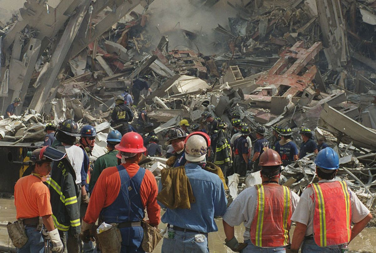 Rescue workers look over the rubble of the World Trade Center towers in New York, Wednesday, Sept. 12, 2001. (AP/Virgil Case)