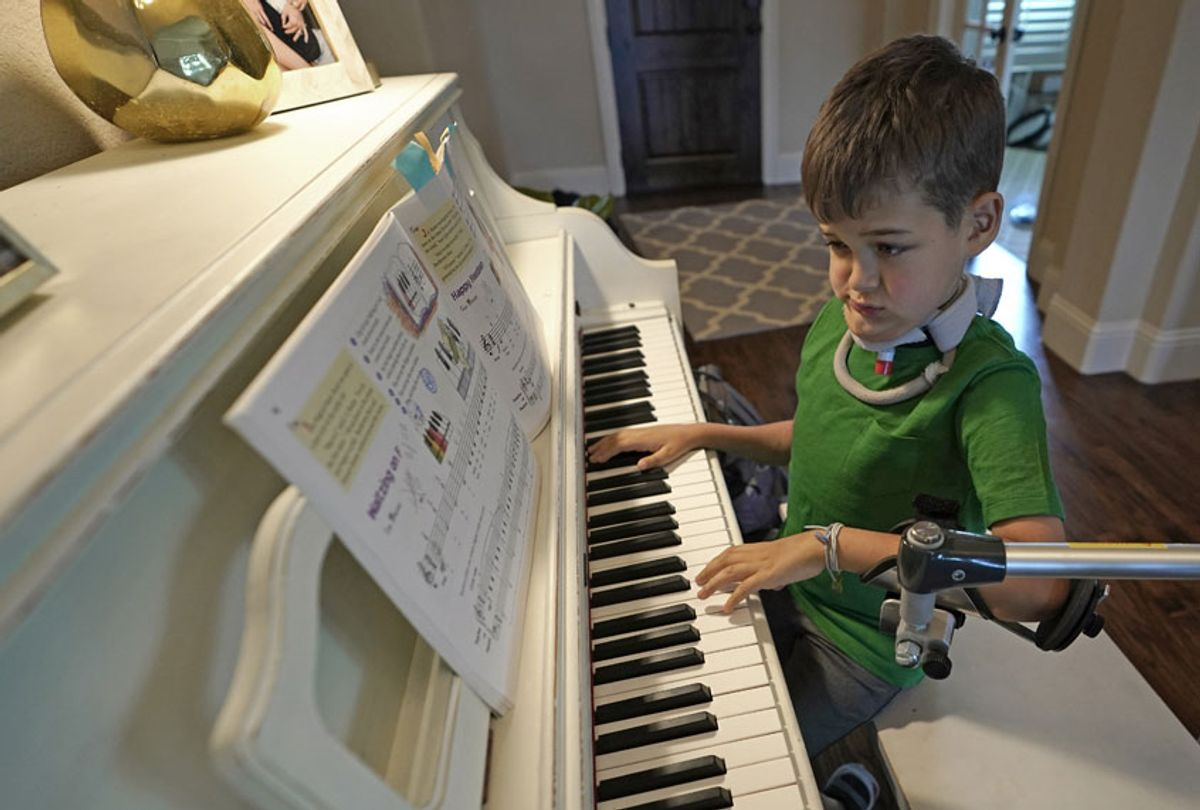 Braden Scott uses a device to support his left arm as he practices on the piano in Tomball, Texas on Friday, March 29, 2019. Braden was diagnosed with the syndrome called acute flaccid myelitis, or AFM, in 2016 and was paralyzed almost completely. (AP/David J. Phillip)