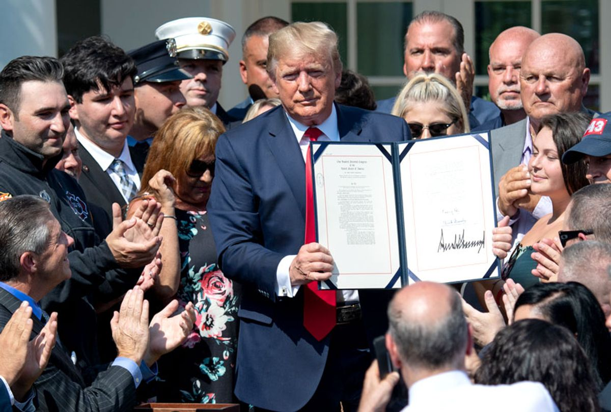 People applaud as US President Donald Trump, surrounded by September 11 first responders and family members, signs HR 1327, an act to permanently authorize the September 11th victim compensation fund, during a ceremony in the Rose Garden of the White House in Washington, DC, July 29, 2019.  (Getty/Saul Loeb)