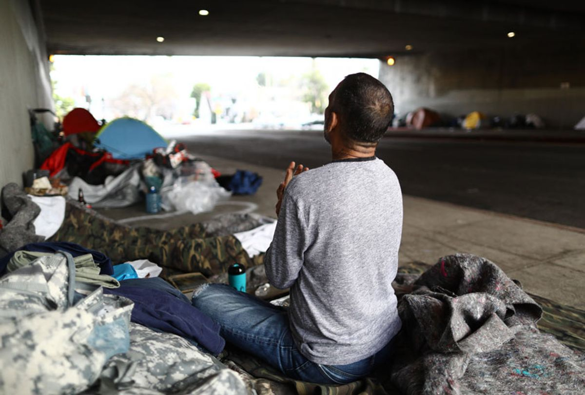 Travis Stanley, who said he has been homeless for three months and is a U.S. Navy veteran, sits on donated bedding, where he normally sleeps, beneath an overpass on June 5, 2019 in Los Angeles, California. (Getty/Mario Tama)
