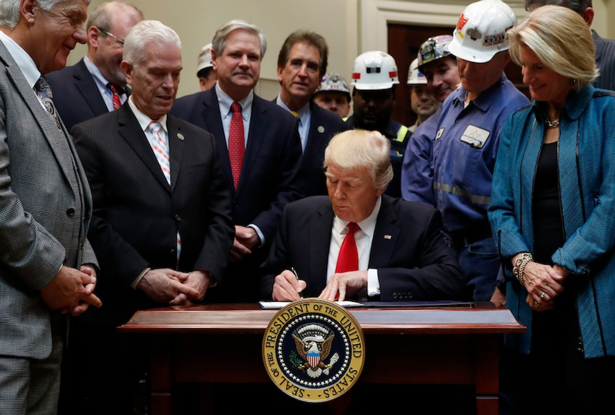 President Donald Trump signs H.J. Res. 38 in the Roosevelt Room of the White House in White House in Washington, Thursday, Feb. 16, 2017.  (AP Photo/Carolyn Kaster)