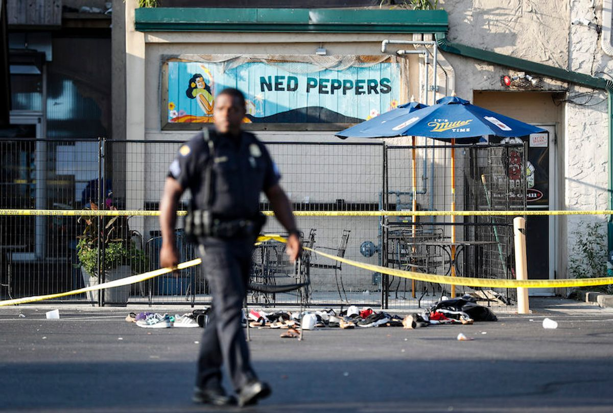 Shoes are piled outside the scene of a mass shooting including Ned Peppers bar, Sunday, Aug. 4, 2019, in Dayton, Ohio.  (AP/John Minchillo)