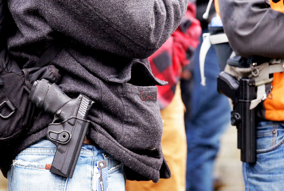 Men stand with pistols strapped at their sides at a gun rights rally on the steps of the Capitol Friday, Jan. 15, 2016, in Olympia, Wash. (AP Photo/Elaine Thompson)