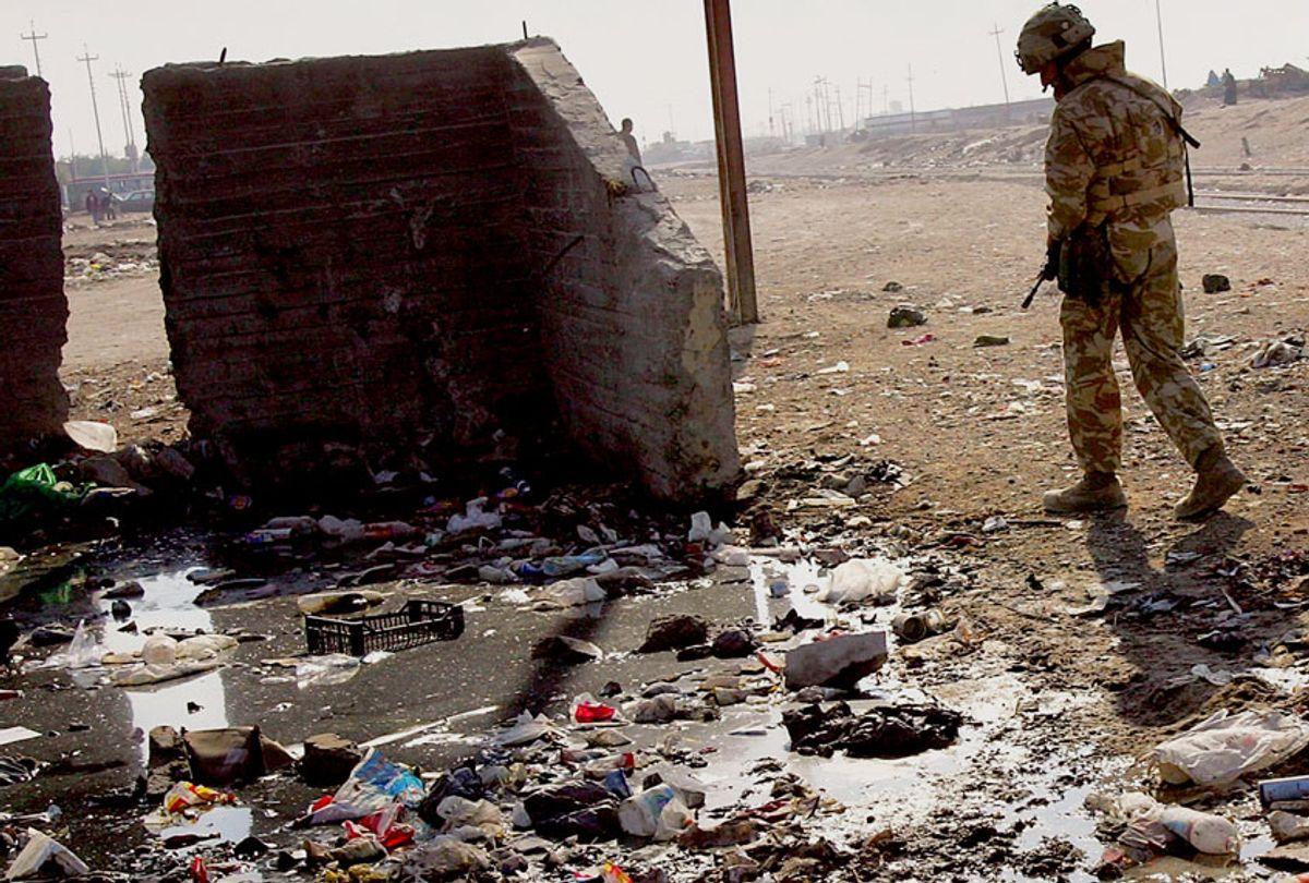 A soldier walks past open sewage on December 14, 2005 in Az Zubayr near Basra in southern Iraq. (John Moore/Getty Images)