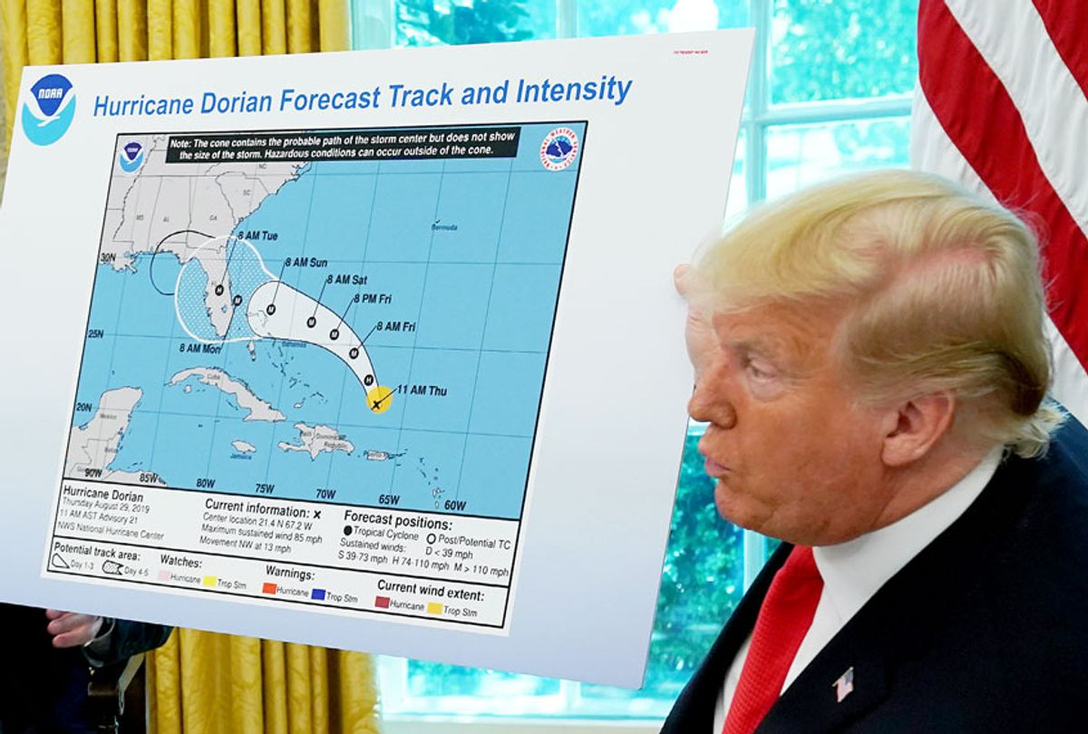 U.S. President Donald Trump (R) references a map while talking to reporters following a briefing from officials about Hurricane Dorian in the Oval Office at the White House September 04, 2019 in Washington, DC.  (Chip Somodevilla/Getty Images)