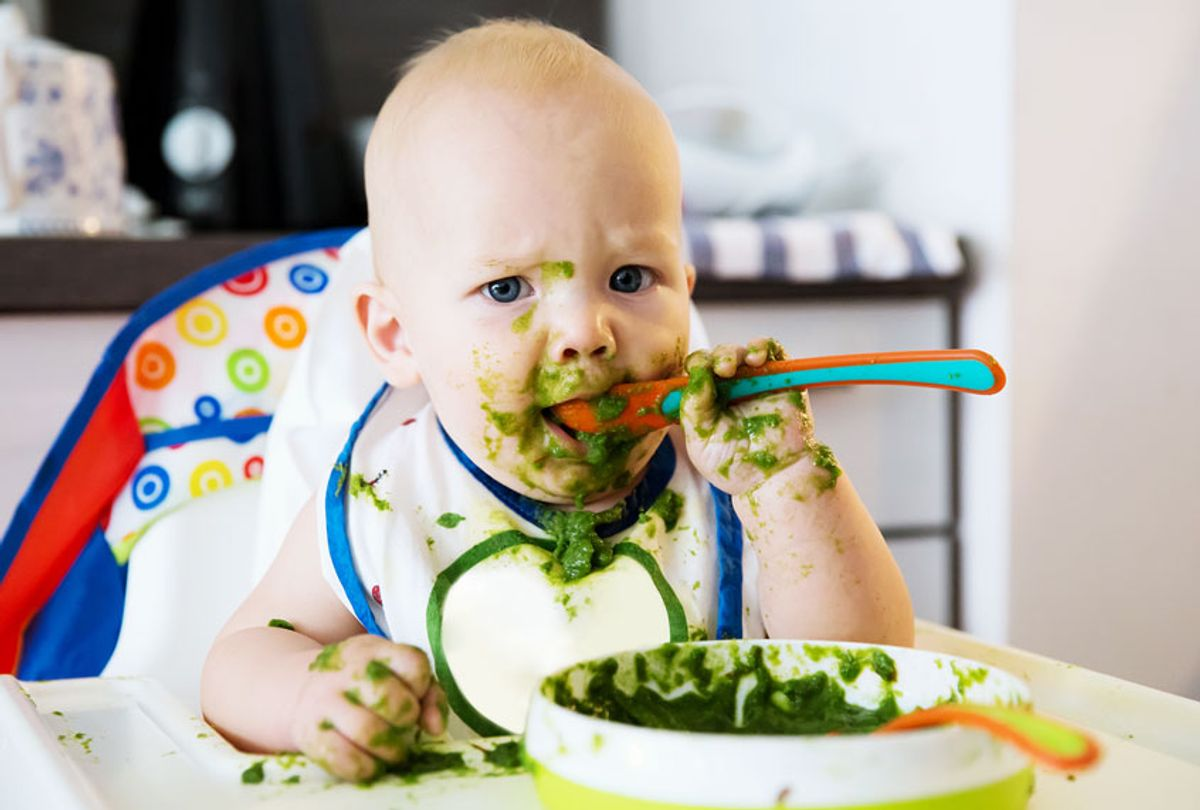Baby eating green mush baby food (Getty Images/iStock)