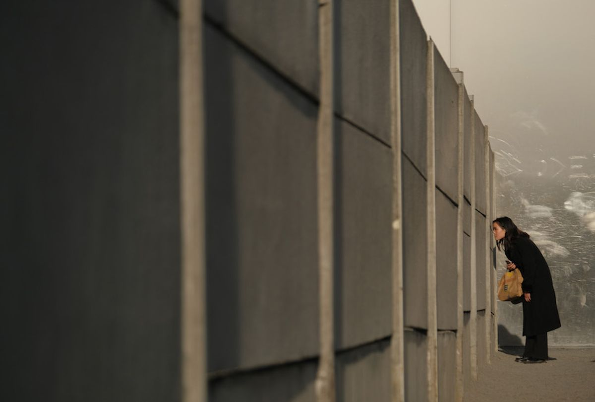 """A visitor peeks through slats in the inner wall into the """"death zone"""" at a preserved portion of the Berlin Wall at Bernauer Strasse on October 31, 2019 in Berlin, Germany. (Sean Gallup/Getty Images)"""