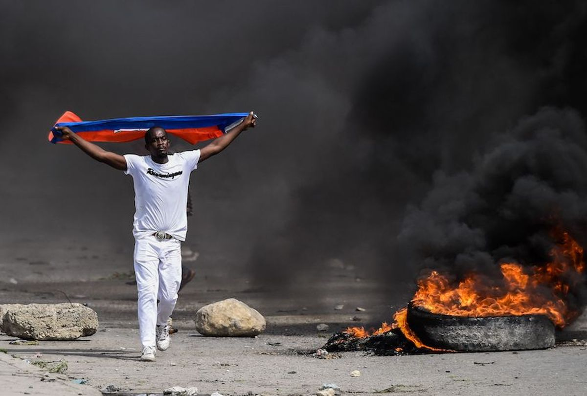 A demonstrator waves a Haitian flag during a protest outside United Nation's main base, against President Jovenel Moise on October 4, 2019 in Port-au-Prince, Haiti.  (Chandan Khanna//AFP via Getty Images)