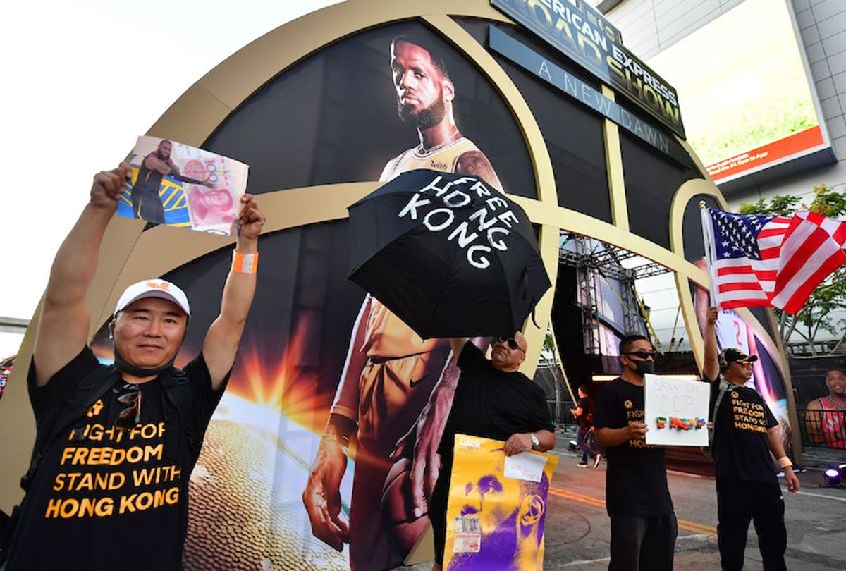 """Hong Kong supporters protest outside Staples Center ahead of the Lakers vs Clippers NBA season opener in Los Angeles on October 22, 2019. - Activists handed out free T-shirts displaying support for the Hong Kong protests after an NBA fan in Northern California raised enough money to pay for more than 10,000 shirts, according to the organizer who goes by the pseudonym """"Sun Lared"""" as LeBron James of the Lakers suffers the brunt of people's anger after comments he made in response to the tweet from Houston Rockets GM Daryl Morey in support of Hong Kong protesters, and drawing the ire of the Chinese Communist Pary. (Photo by Frederic J. BROWN / AFP) (Photo by FREDERIC J. BROWN/AFP via Getty Images) (Frederic J. Brown/AFP via Getty Images)"""