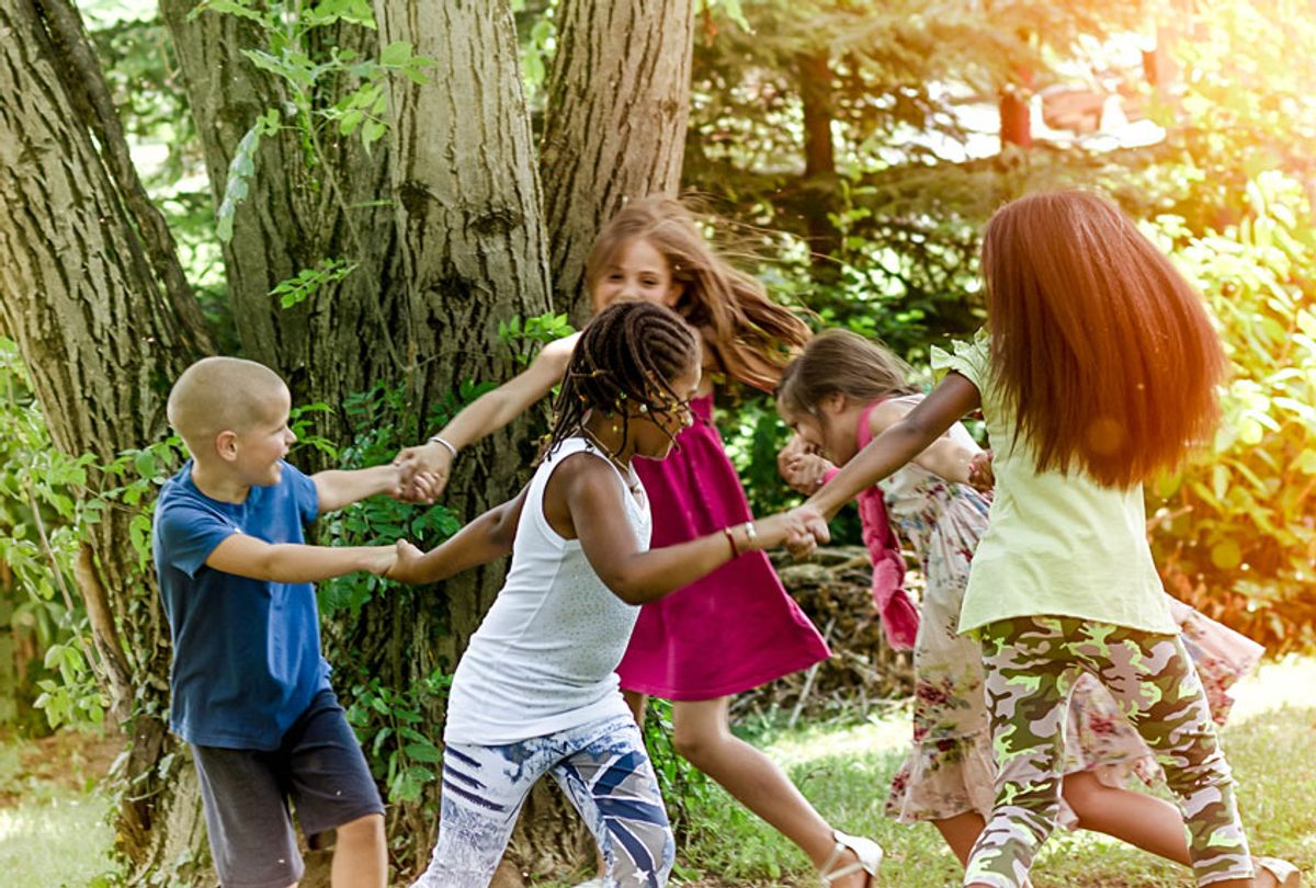 Children holding hands and running through the park. (Getty Images)