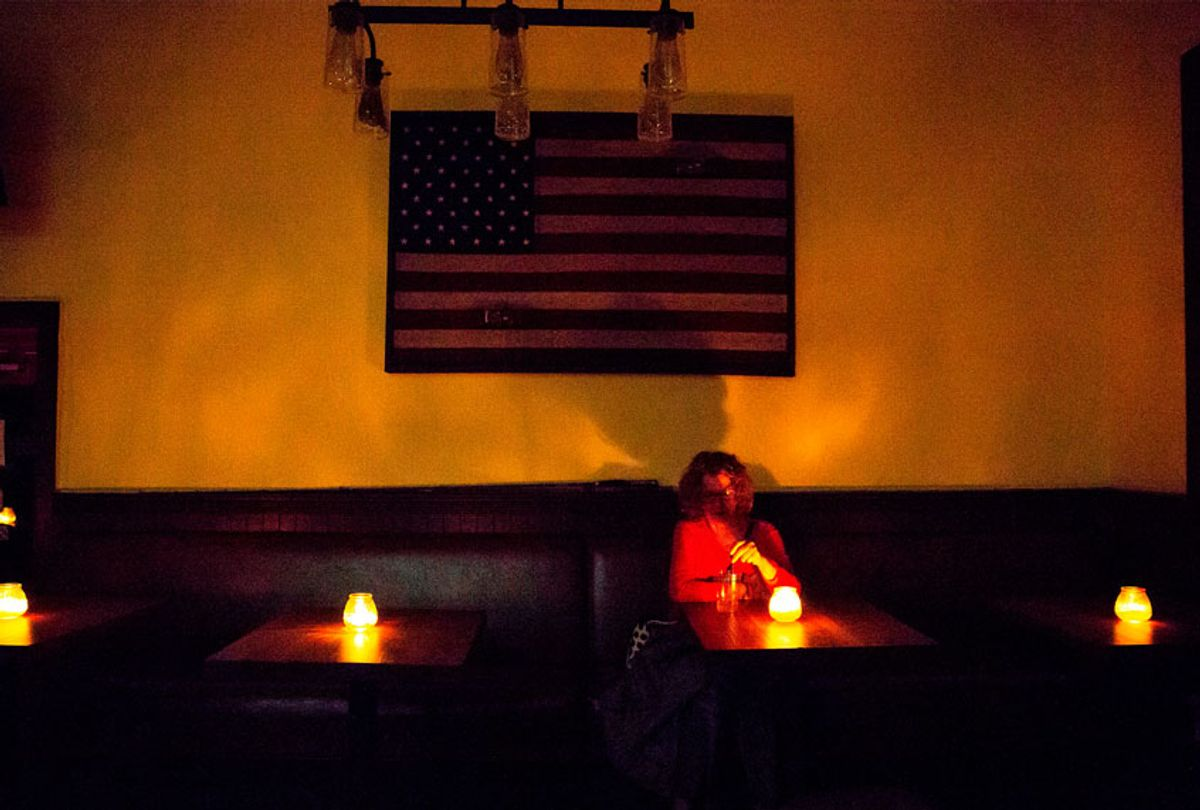 Judy Aquiline, a Sonoma local, sits in the candle-lit restaurant Reel and Brand in Sonoma, California, on October 9, 2019, during a planned power outage by the Pacific Gas & Electric (PG&E) utility company. - Rolling blackouts set to affect millions of Californians began on October 9 as a utility company started switching off power to an unprecedented number of households in the face of hot, windy weather that raises the risk of wildfires.  (BRITTANY HOSEA-SMALL/AFP via Getty Images)