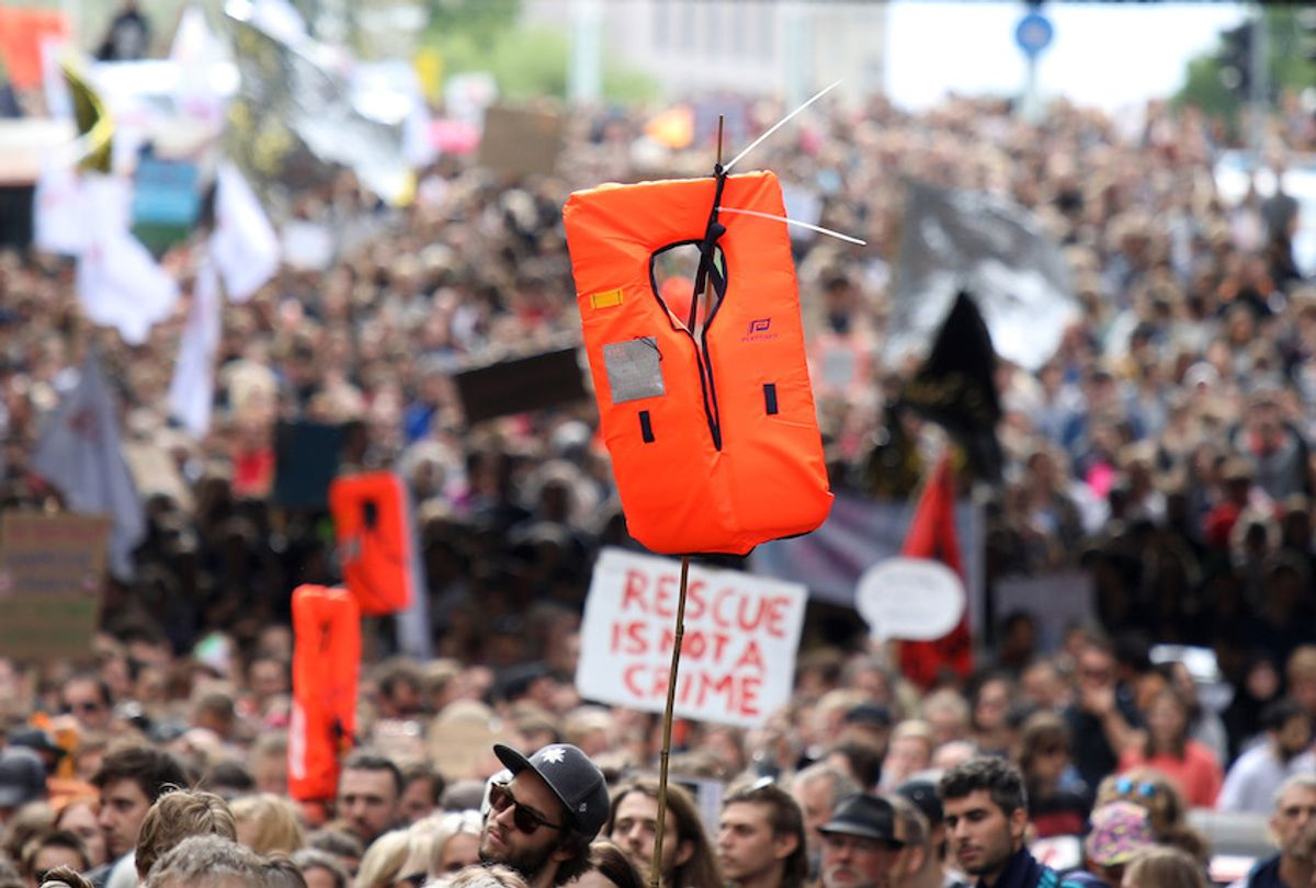 Supporters of the NGO Sea-Watch hold flags and rescue blankets during a demonstration in solidarity with the German captain of rescue vessel Sea-Watch 3, Carola Rackete, on July 6, 2019 outside the Chancellery in Berlin. (Omer Messinger/AFP via Getty Images)