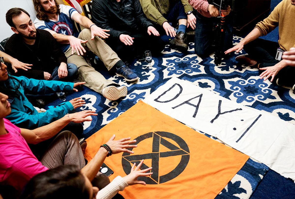 """Extinction Rebellion protestors participate in a hunger strike and """"grief session"""" in House Speaker Nancy Pelosi's Office in Longworth House Office Building on November 18, 2019 in Washington, DC. The strike is planned to be held all week or until Speaker Pelosi agrees to sit with the group for a one hour on-camera interview about climate change.  (Sarah Silbiger/Getty Images)"""