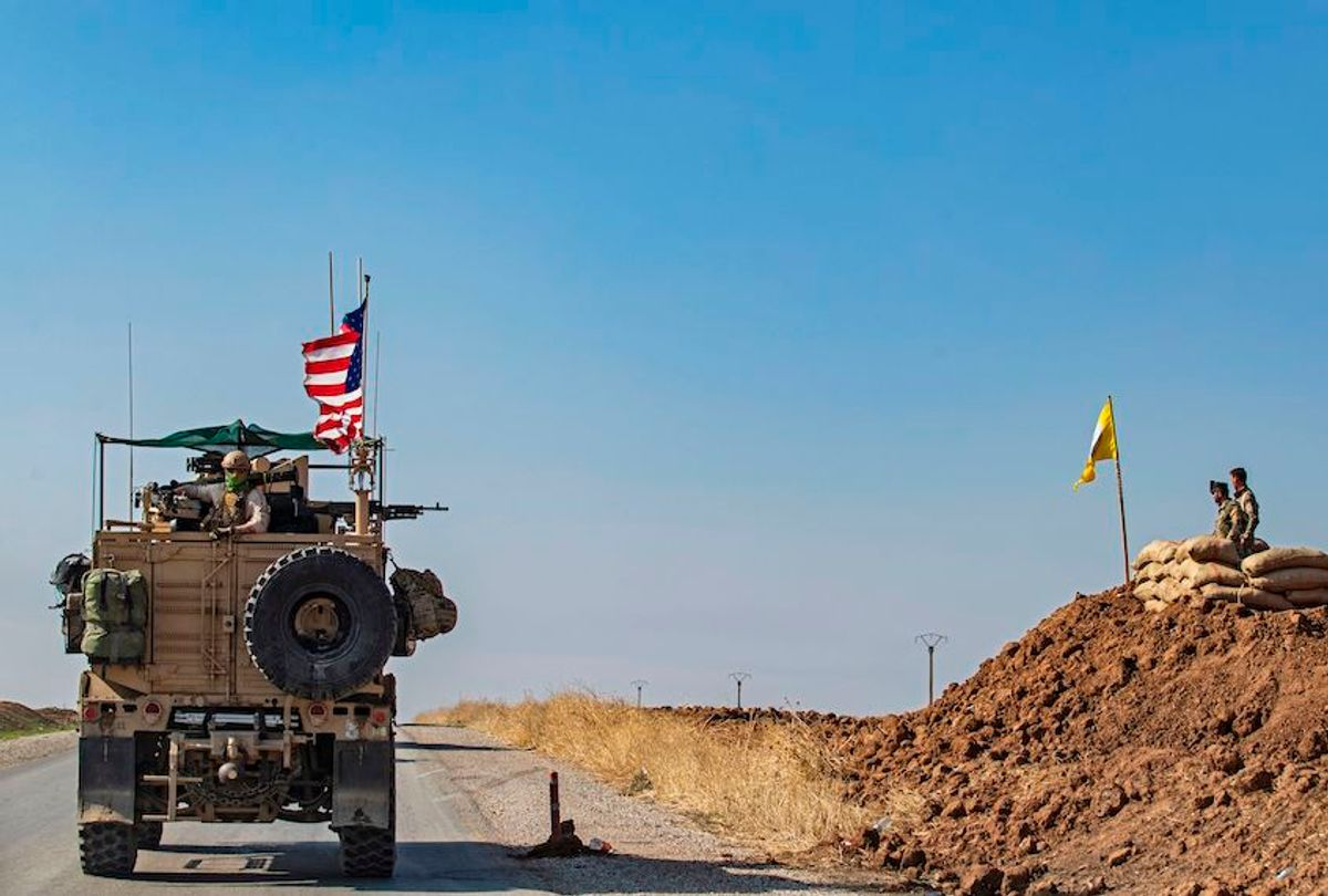 A US armoured vehicle drives past members of the Syrian Democratic Forces (SDF), during a patrol of the Syrian northeastern town of Qahtaniyah at the border with Turkey, on October 31, 2019. - US forces accompanied by Kurdish fighters of the Syrian Democratic Forces (SDF) patrolled part of Syria's border with Turkey, in the first such move since Washington withdrew troops from the area earlier this month, an AFP correspondent reported. (Photo by Delil SOULEIMAN / AFP) (Photo by DELIL SOULEIMAN/AFP via Getty Images) (Delil Souleiman/AFP via Getty Images)