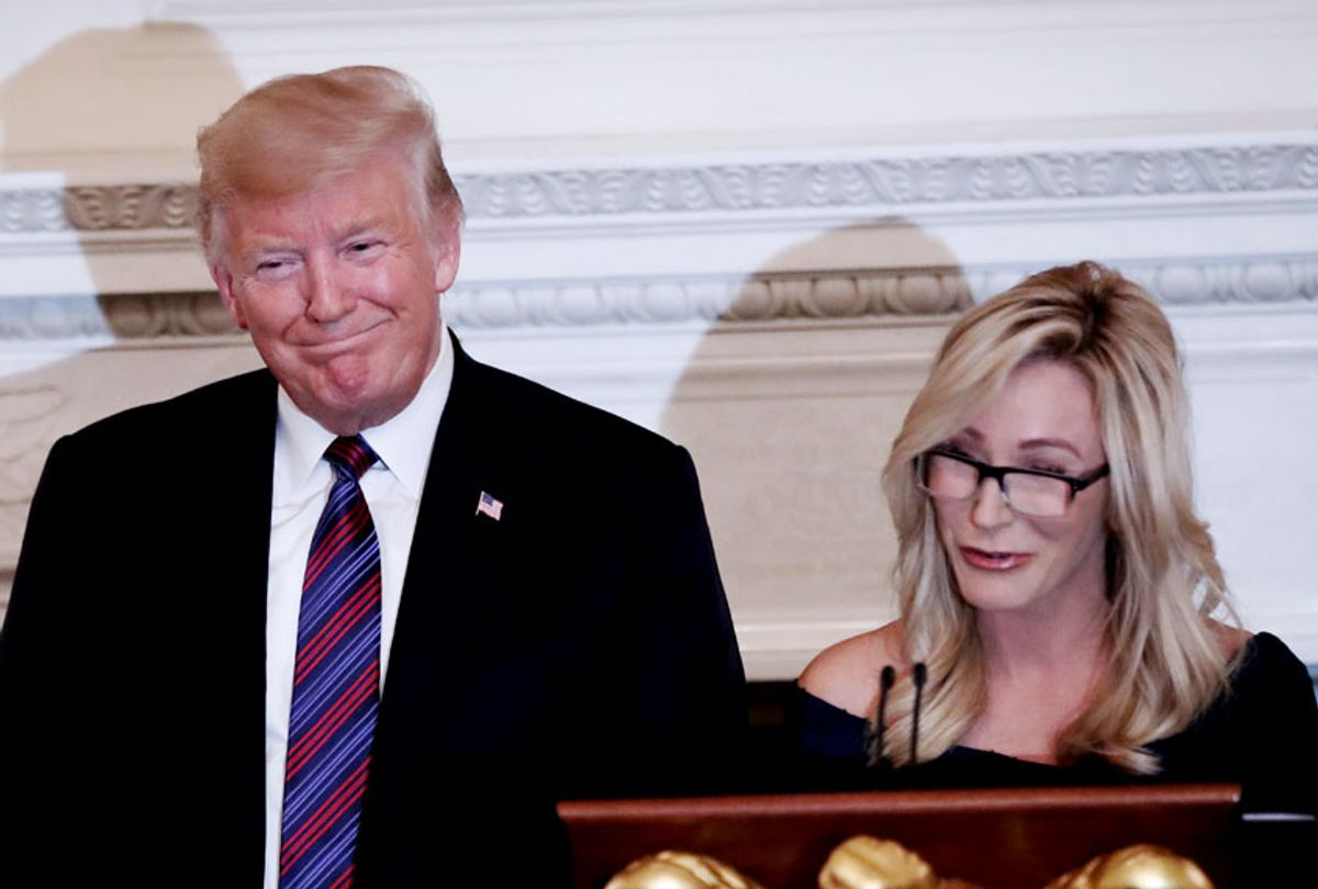President Donald Trump smiles as pastor Paula White prepares to lead the room in prayer, during a dinner for evangelical leaders in the State Dining Room of the White House, Monday, Aug. 27, 2018, in Washington. () (AP Photo/Alex Brandon)