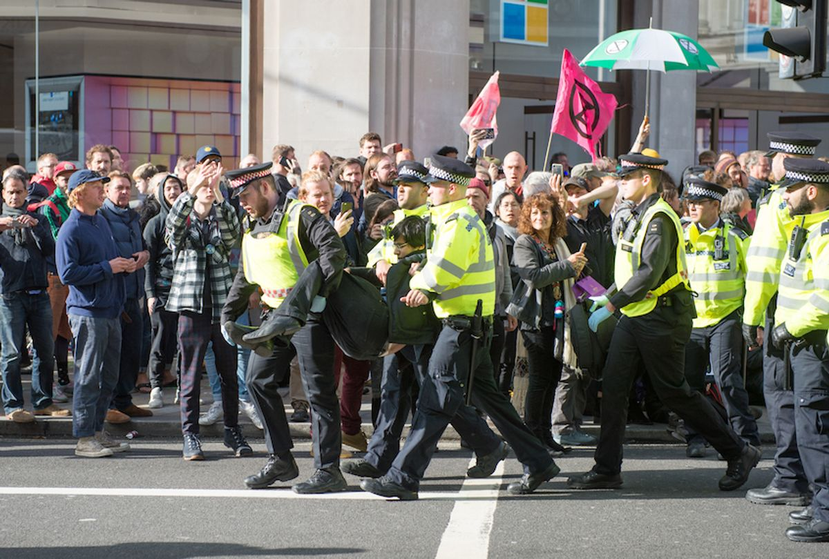 Police arrest an activist as hundreds of members of the Extinction Rebellion environmental activist group swarm Oxford circus with three activists erecting a road blocking wooden pyramid structure with an upside down tree hanging in the middle on October 18, 2019 in London, England. (Photo by Ollie Millington/Getty Images)