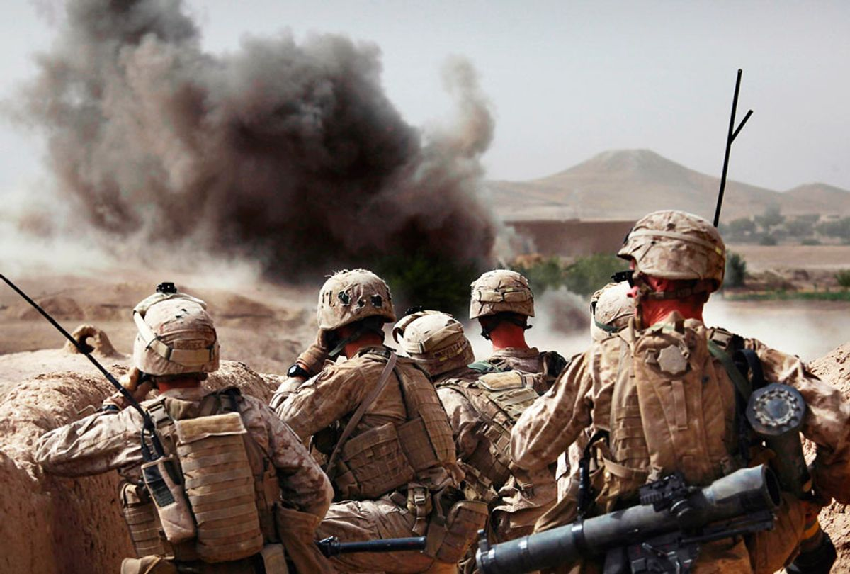United States Marines from Bravo Company of the 1st Battalion of the 2nd Marines watch the explosion after calling in an airstrike during a gunbattle as part of an operation to clear the area of insurgents near Musa Qaleh, in northern Helmand Province, southern Afghanistan (AP Photo/Kevin Frayer)