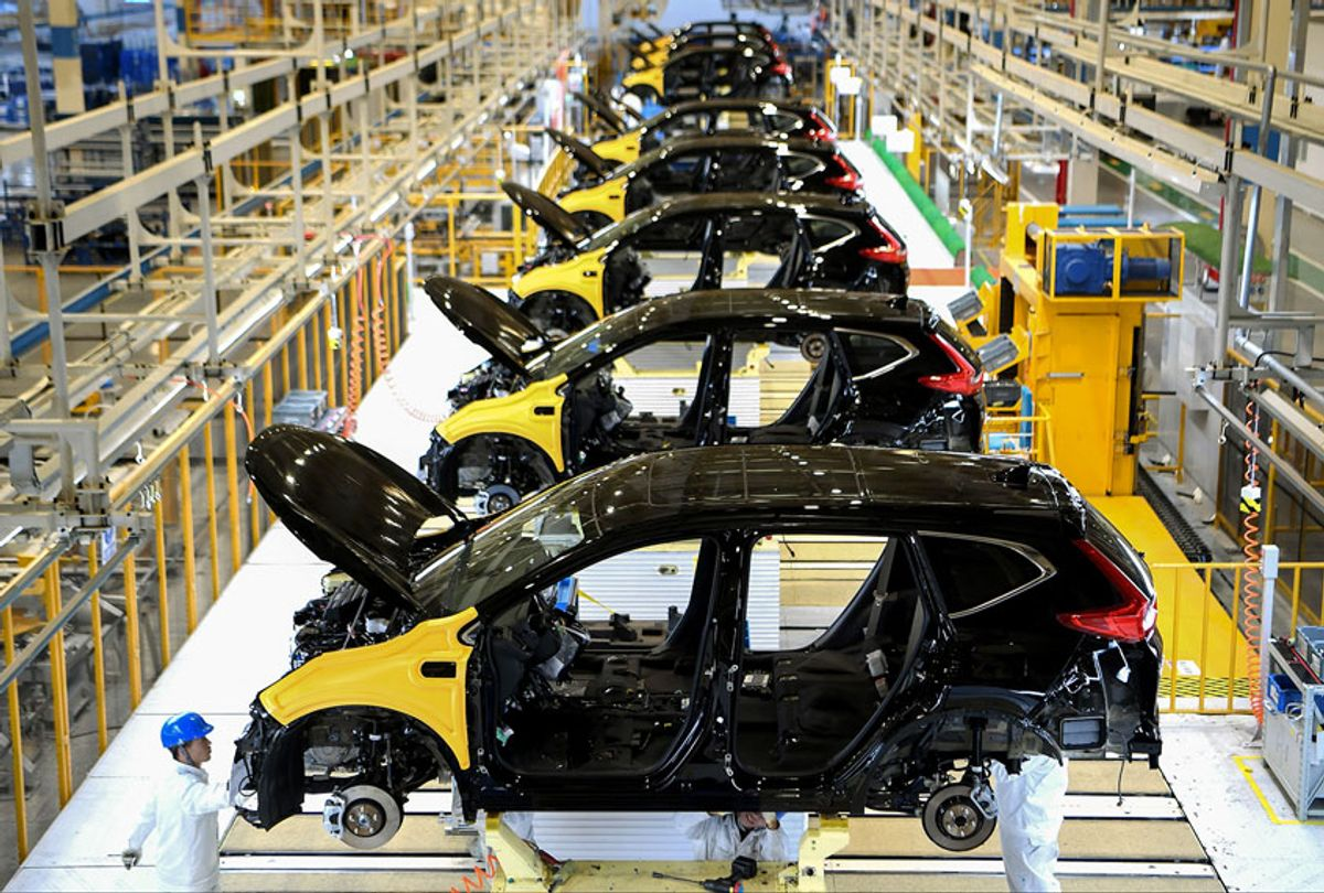 Employees working on an assembly line at an Auto Plant (STR/AFP via Getty Images)