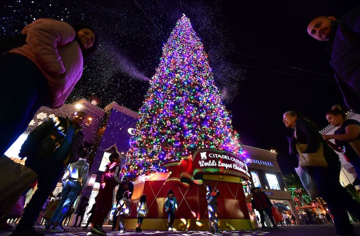 """Children get excited by the artificial snow spewing from the """"World's Tallest live-cut Christmas Tree,"""" standing 115 feet and decorated with some 18,000 multi-colored LED lights, at the Citadel Outlets shopping plaza in Los Angeles, California on December 17, 2019. (Photo by Frederic J. BROWN / AFP) (Photo by FREDERIC J. BROWN/AFP via Getty Images) (Frederic J. Brown/AFP via Getty Images)"""