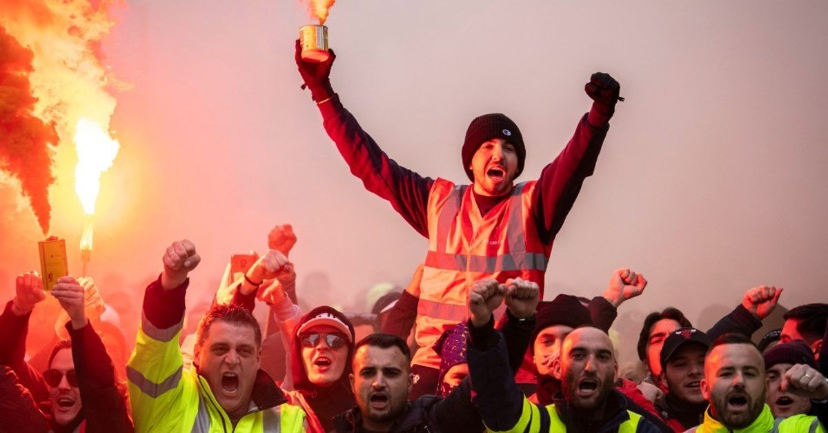 A protester holds a flare as public and private workers demonstrate and shout slogans during a mass strike against pension reforms on Dec. 5, 2019 in Marseille, France.  (Arnold Jerocki/Getty Images)