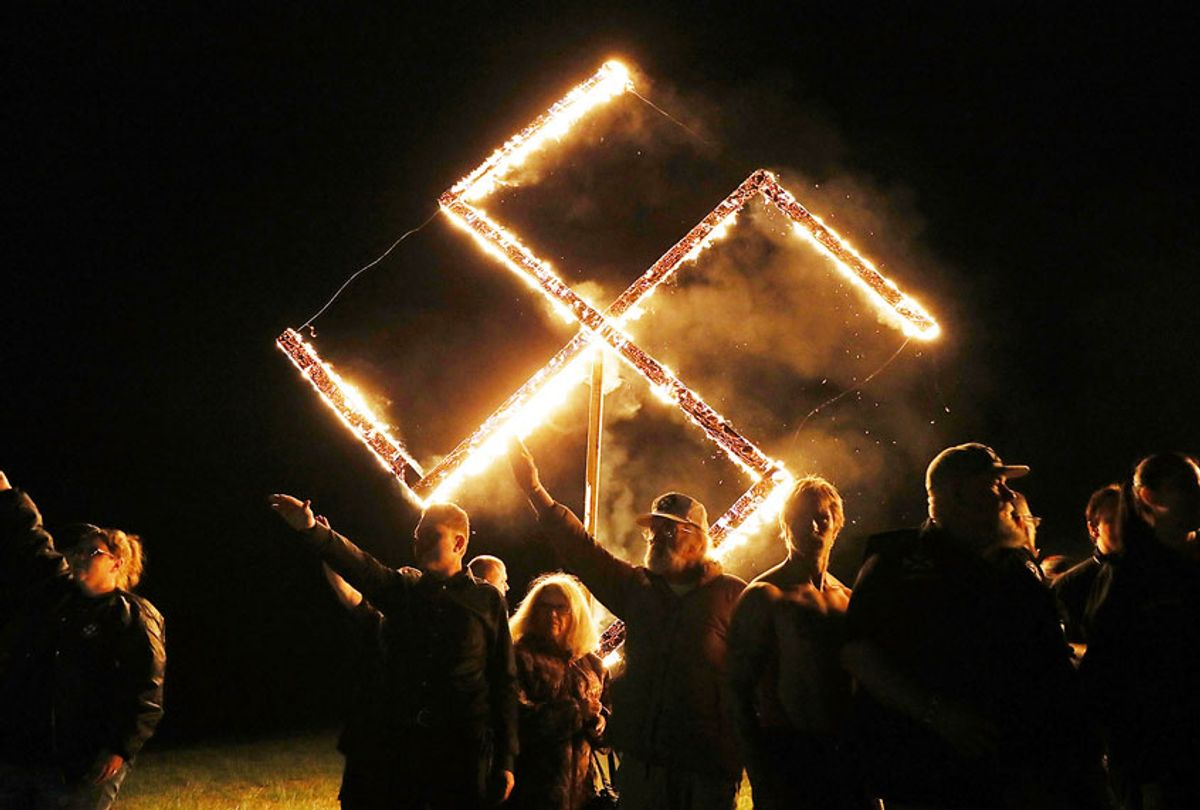 Members of the National Socialist Movement, one of the largest neo-Nazi groups in the US, hold a swastika burning after a rally on April 21, 2018 in Draketown, Georgia. Community members had opposed the rally in Newnan and came out to embrace racial unity in the small Georgia town. Fearing a repeat of the violence that broke out after Charlottesville, hundreds of police officers were stationed in the town during the rally in an attempt to keep the anti racist protesters and neo-Nazi groups separated. (Spencer Platt/Getty Images)