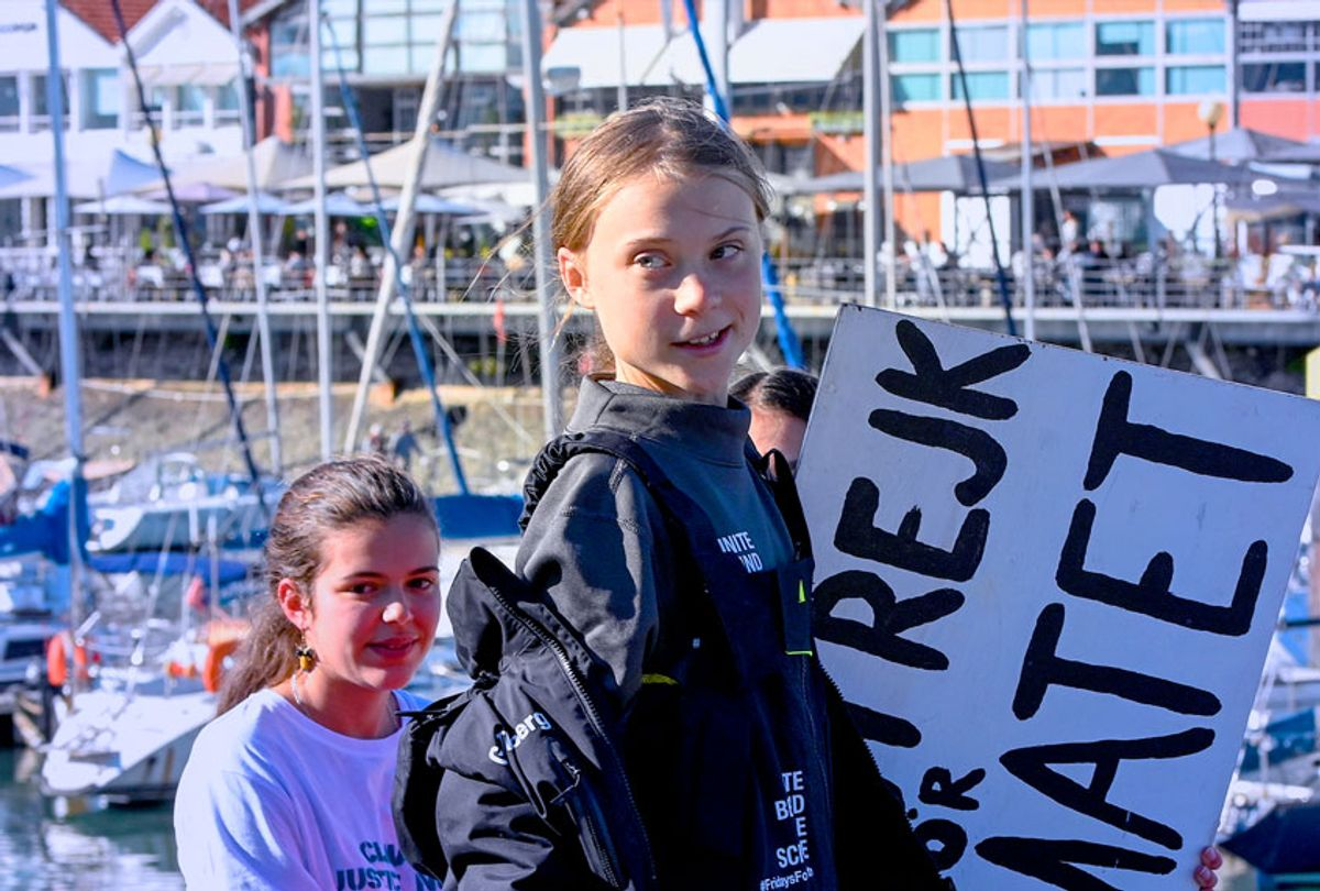 """Swedish teen climate activist Greta Thunberg carries the placard """"School strike for the climate"""" which she held outside the Swedish parliament, upon her arrival in Santo Amaro Recreation dock on December 03, 2019 in Lisbon, Portugal. Greta Thunberg sailed from Norfolk, Virginia, USA , accompanied by her father Svante Thunberg on the French built Outremer 45 catamaran La Vagabonde, skippered by Australian Riley Whitelum, and is on her way to attend COP25 in Madrid, Spain. (Horacio Villalobos/Getty Images)"""