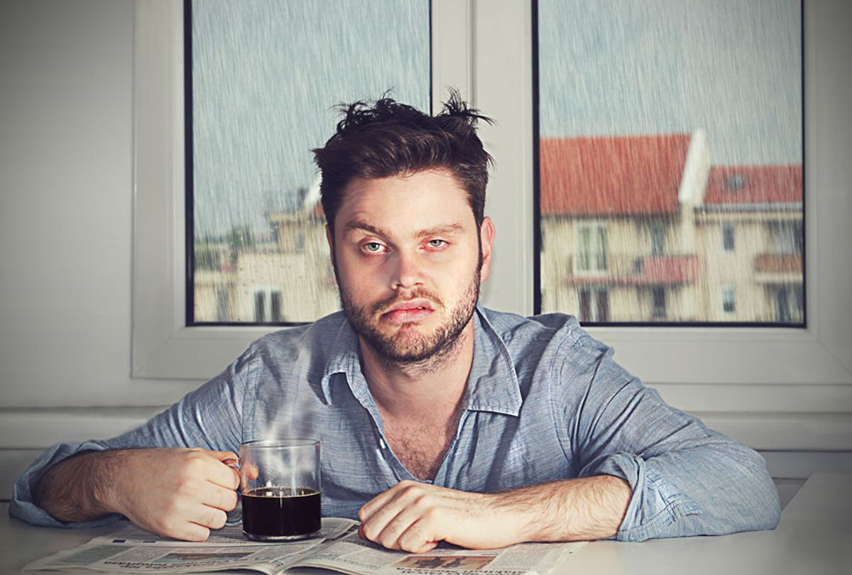 Grumpy hungover man with coffee (Getty Images)