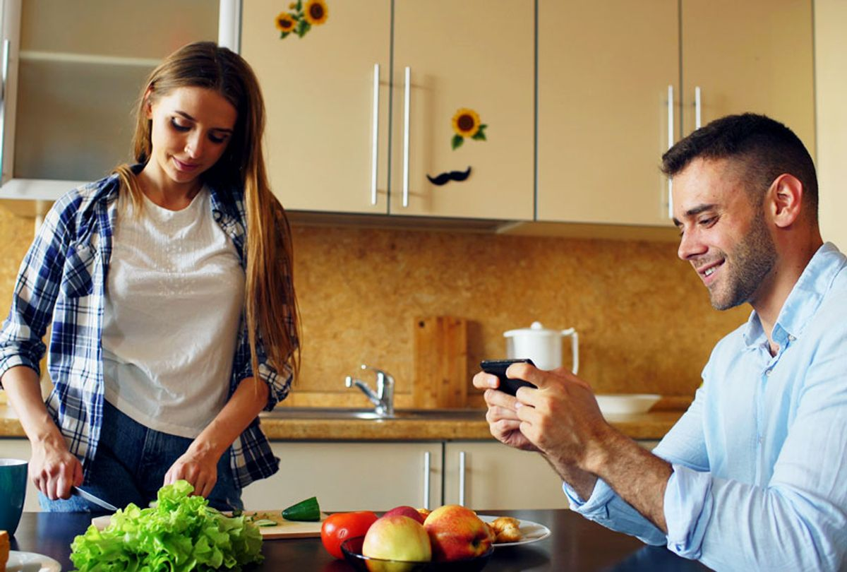 Man playing video game on smartphone while his girlfriend cooking (Getty Images)