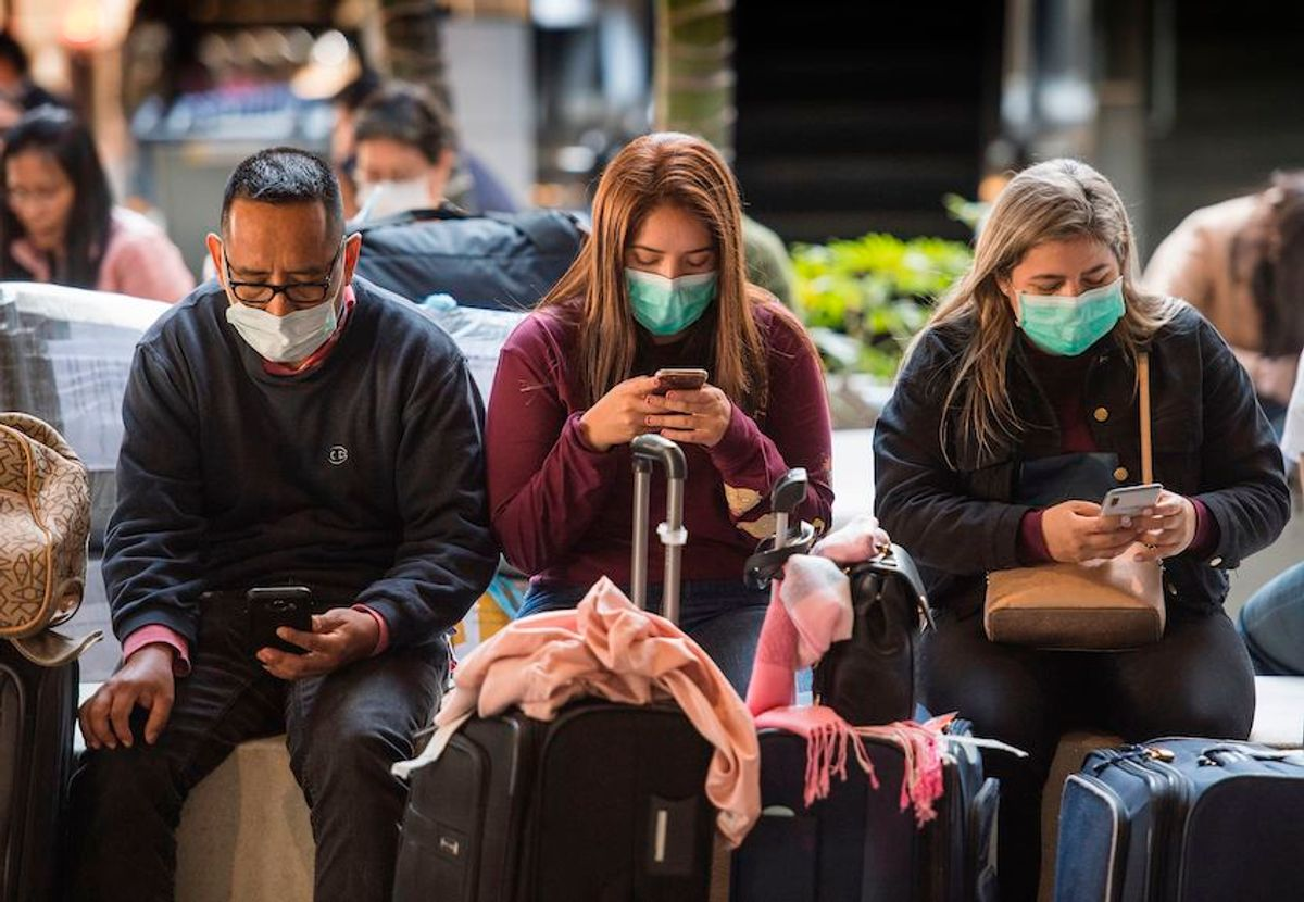 Passengers wear face masks to protect against the spread of the Coronavirus as they arrive on a flight from Asia at Los Angeles International Airport, California, on January 29, 2020. (Mark Ralston/AFP via Getty Images)