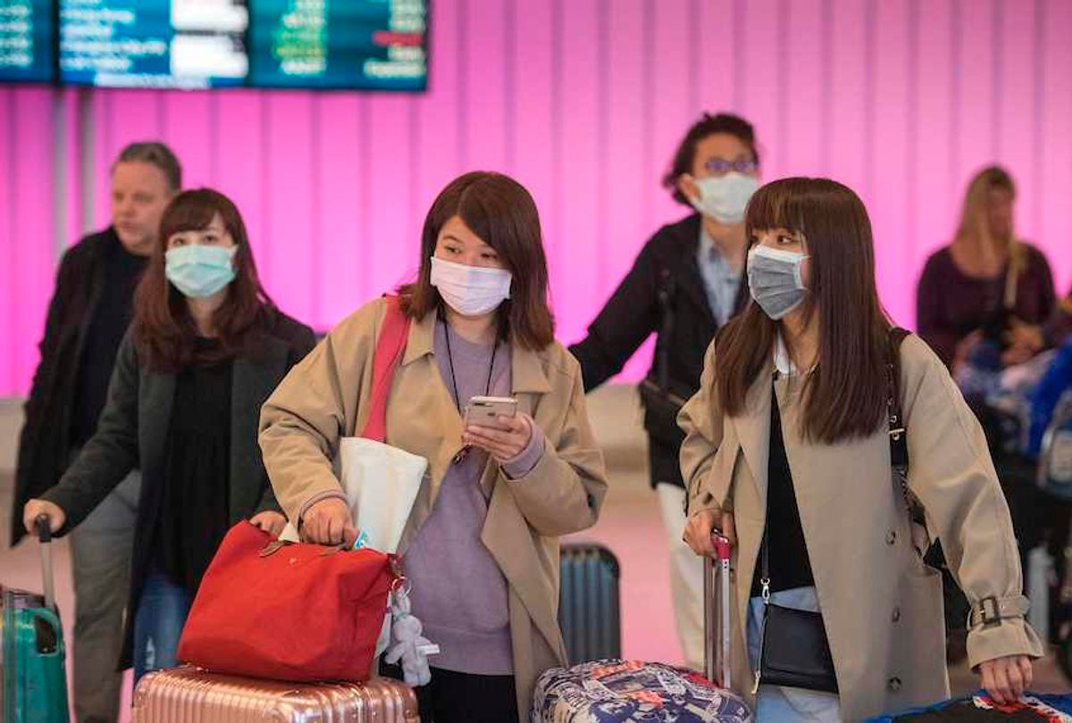 Passengers wear protective masks to protect against the spread of the Coronavirus as they arrive at the Los Angeles International Airport, California, on January 22, 2020. (Mark Ralston/AFP via Getty Images)