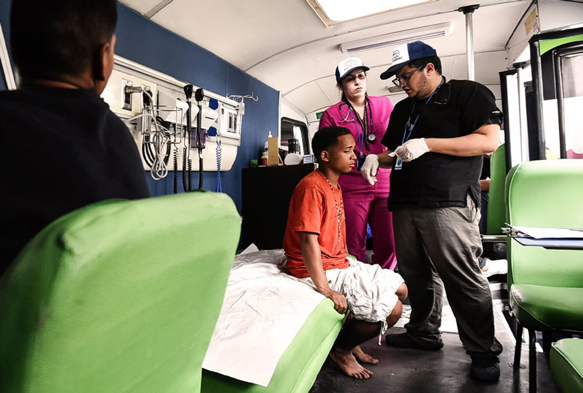 Doctors treat a homeless person suffering from an ear infection on July 25, 2019 in Caracas, Venezuela. Panabus is a network of assistance for homeless people, which seeks to enhance the dignity of those who care for, offering through mobile units the basic services of: personal hygiene, primary medical care and community kitchen. (Carolina Cabral/Getty Images)