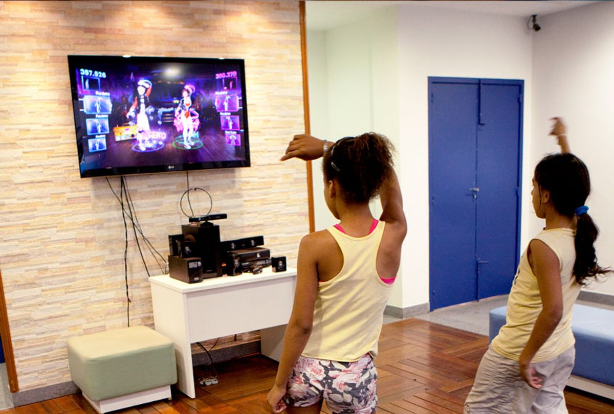 Poor children from favela Complex Alemao dance to an Xbox game in a community center, on September 13, 2012 in Rio de Janeiro, Brazil. The Plaza of Knowledge was built by the municipal government. Favelas are informal settlements, traditionally without electricity, water and sewage services. This favela got a park, learning center, cinema and cable car as part of infrastructure improvements. The learning center has courses and computers available to locals.  (Melanie Stetson Freeman/The Christian Science Monitor via Getty Images)