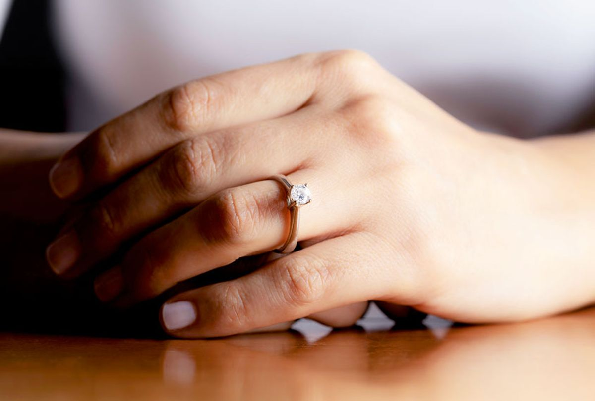 Close up of womans hand wearing an engagement ring. (Getty Images)
