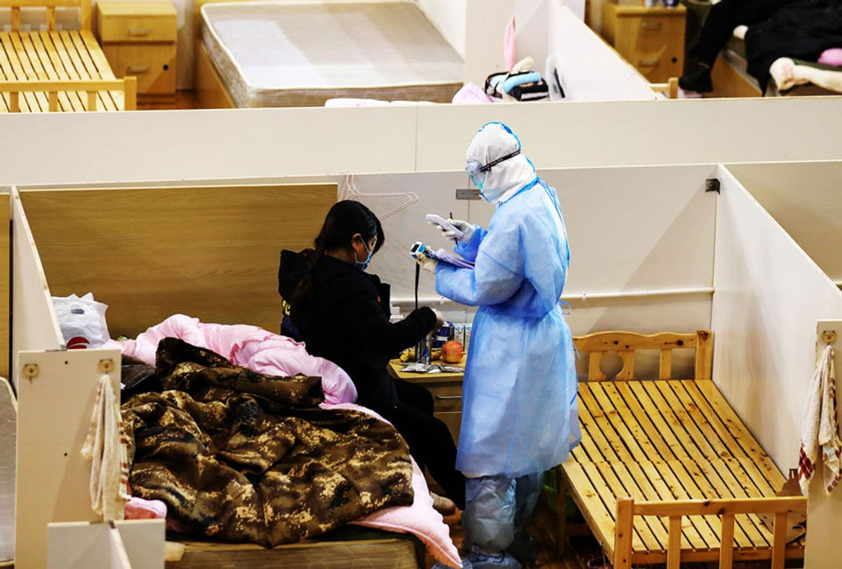 A nurse checks a patient in a temporary hospital for the COVID-19 patients set up in a gymnasium in Wuhan in central China's Hubei province Thursday, March 05, 2020. Most of the patients have been discharged, and only about one hundred are still there. (Feature China/Barcroft Media via Getty Images)