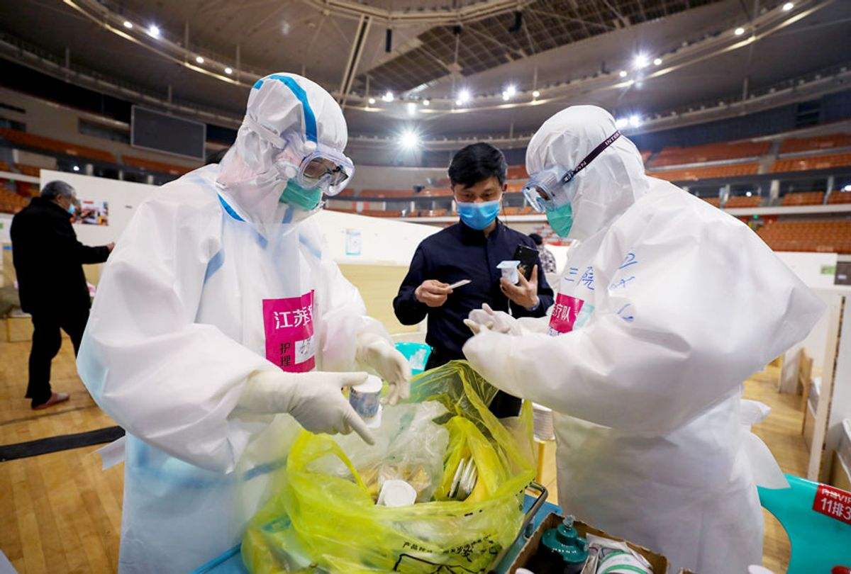 This photo taken on March 5, 2020 shows nurses preparing to deliver yoghurt to patients at a temporary hospital set up for COVID-19 coronavirus patients in a sports stadium in Wuhan, in China's central Hubei province. - China reported 30 more deaths from the new coronavirus outbreak on March 6, with fresh infections rising for a second straight day and 16 new cases imported from overseas.  (STR/AFP via Getty Images)