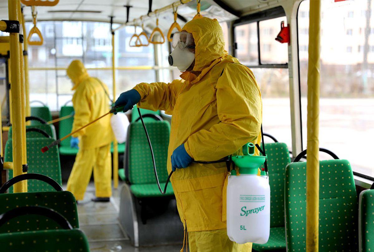 Employees wearing protective gear spray disinfectant to sanitize a passenger bus as a preventive measure against the coronavirus in Lviv, Ukraine, Tuesday, March 3, 2020. Ukrainian Chief sanitary and epidemiological doctor Viktor Liashko has just reported its first confirmed case of the new COVID-19 coronavirus, saying a man who recently arrived from Italy was diagnosed with the virus.  (AP Photo/Mykola Tys)