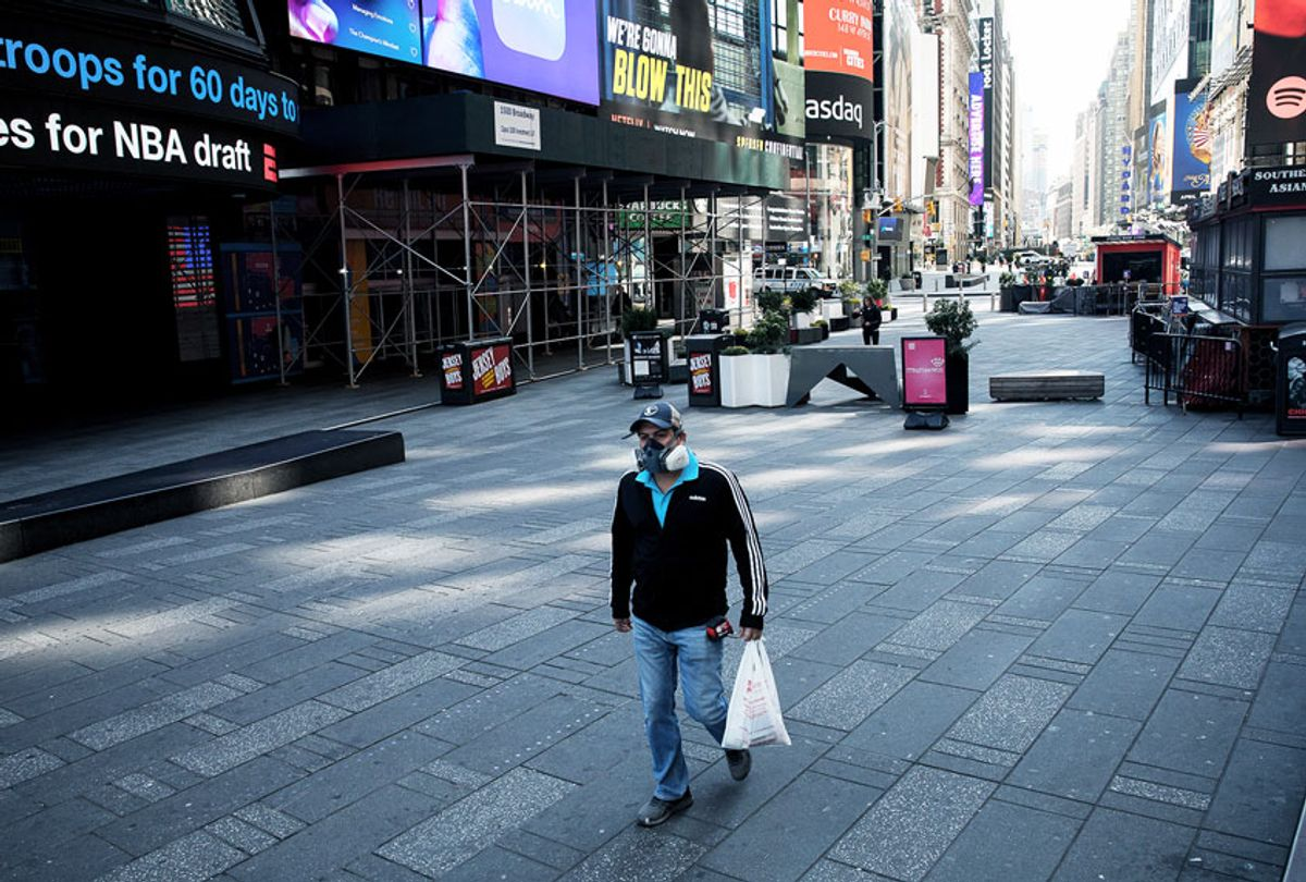 A man wearing a respirator walks through an eerily empty Times Square in New York, the United States, March 26, 2020 (Xinhua/M IchaelNagle/wangying via Getty Images)