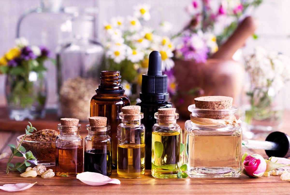 Selection of essential oils with various herbs and flowers in the background (Getty Images/Madeleine Steinbach)