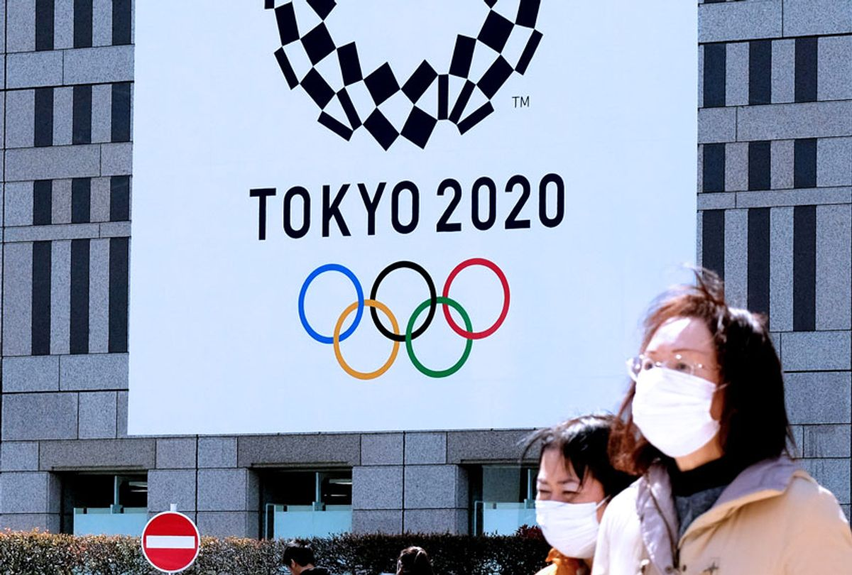 Pedestrians wearing face mask walk before the logo of the Tokyo 2020 Olympic Games displayed on the Tokyo Metropolitan Government building in Tokyo on March 24, 2020. (KAZUHIRO NOGI/AFP via Getty Images)