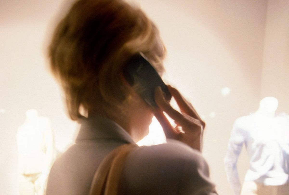 Woman talking on a cell phone, rear view (defocused) (Getty Images/ Brad Rickerby)