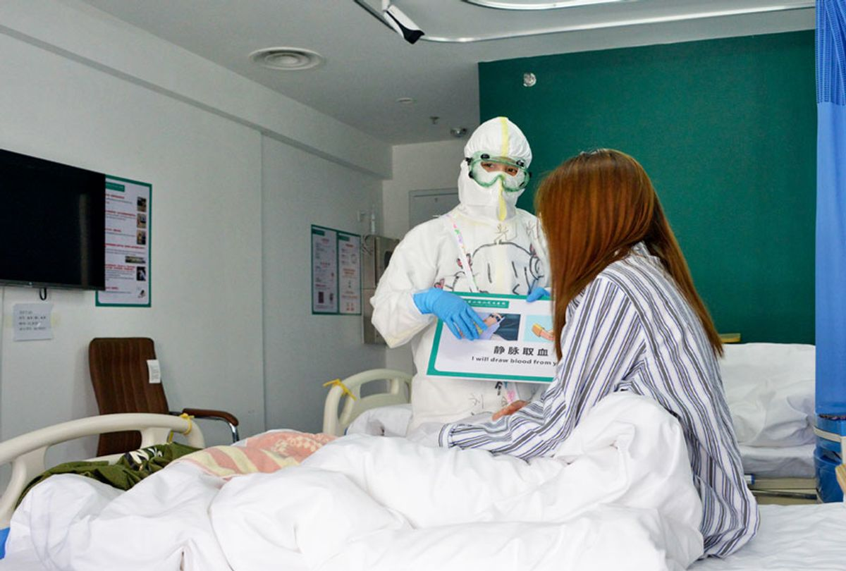 A medical worker communicates with a patient at Xiaotangshan Hospital in Beijing, capital of China, March 30, 2020 (Xinhua/Chen Zhonghao via Getty Images)