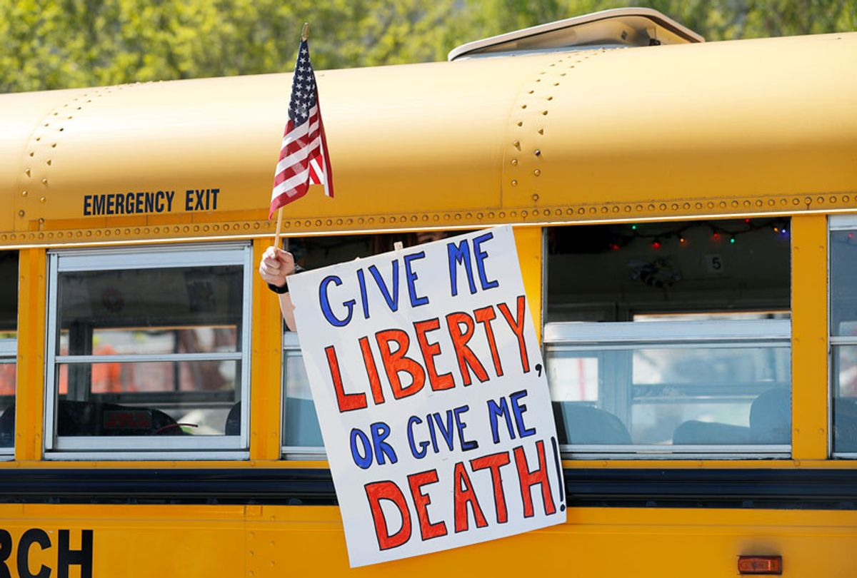 A person holds a sign while waving a flag in the direction of people gathered to voice their opposition to stay-at-home orders put into place due to the COVID-19 outbreak outside the Missouri Capitol (AP Photo/Jeff Roberson)