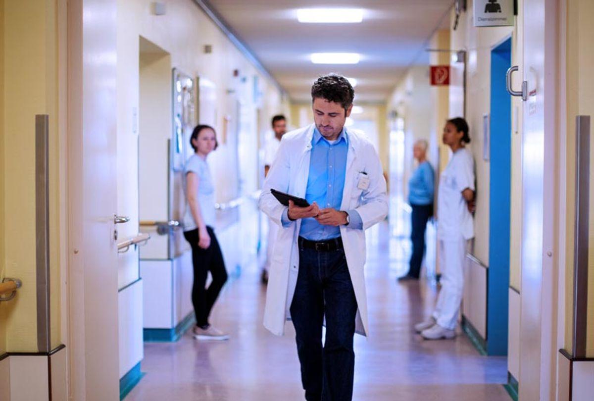 Doctor walking through hospital corridor (Getty Images)