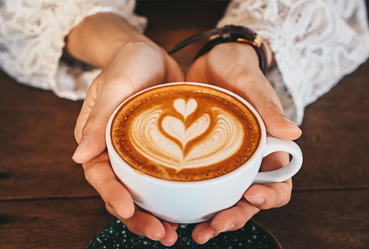 A woman's hands holding a cup of hot latte coffee in her hands (Getty Images)