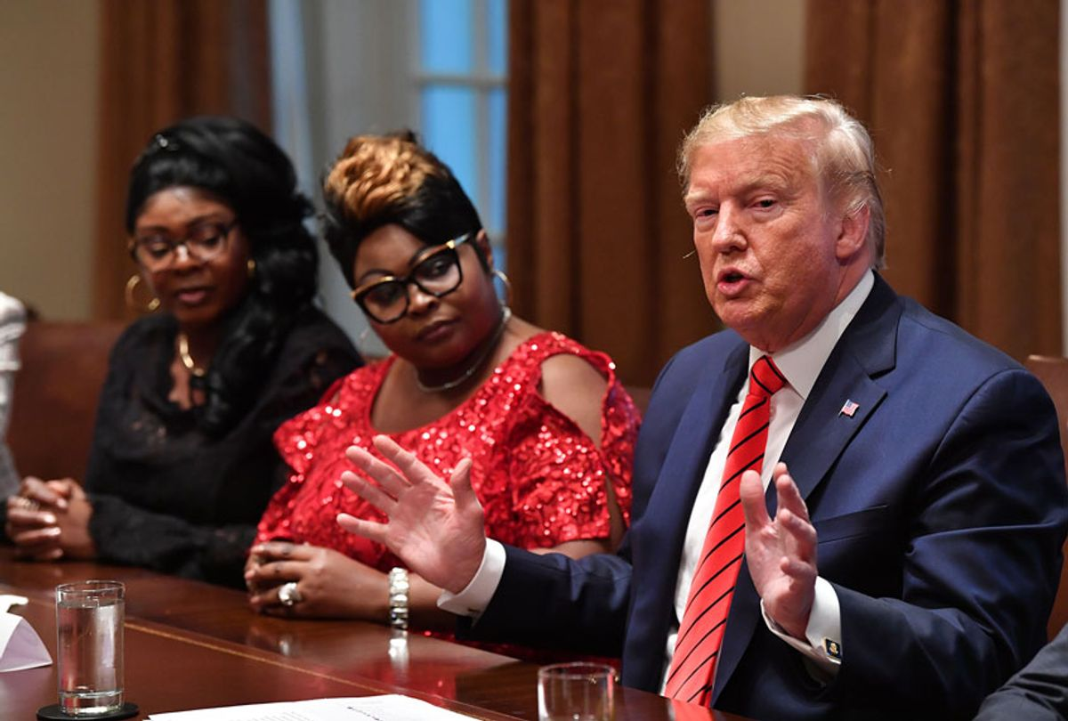 US President Donald Trump speaks as social media personalities Lynnette Hardaway (L) and Rochelle Richardson (2-L), otherwise known as Diamond and Silk listen (NICHOLAS KAMM/AFP via Getty Images)